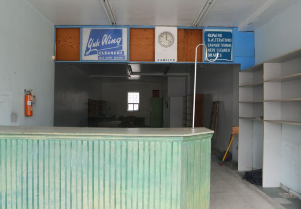 interior of now closed dry cleaners, looking through the front window of Yuk Wing cleaners, pale green counter, old signs, still remain