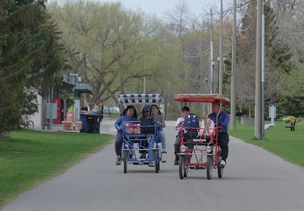 people cycling in 2 quadricycles, a four wheeled bicycle like vehicle, on paths,