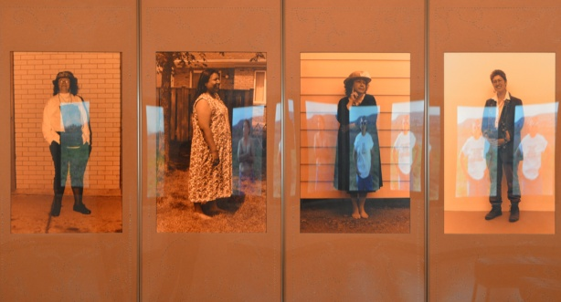 four pictures of women, standing, matted in orange, orange tone to the photos, relfections of other photos in the glass, art by Shelley Niro