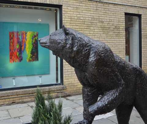 statue of a bear outside, life size, a painting in a glass enclosed box is behind him
