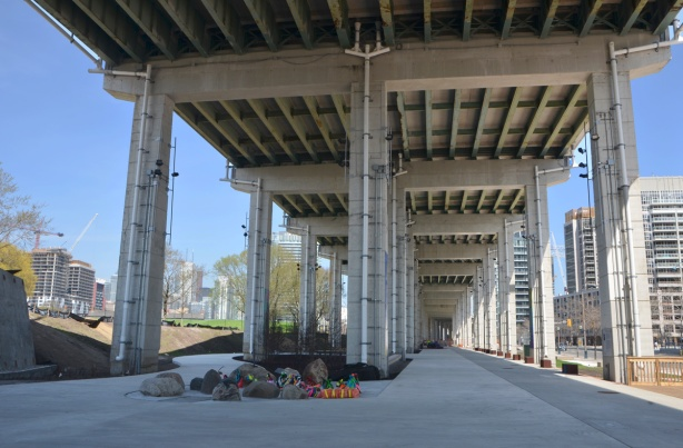 concrete path winds under the bents and pillars of the Gardiner Expressway