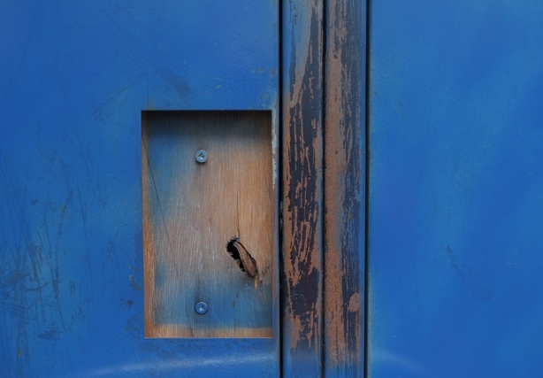 blue abstract from two blue doors with cut out where handle should be