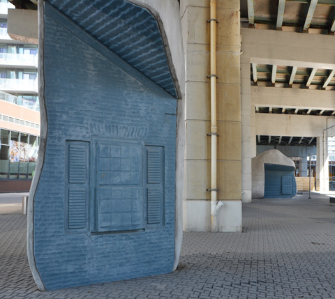 blue surface, window relief sculpture in it, other side is artifical rock, under the Gardiner Expressway, lock stone ground,