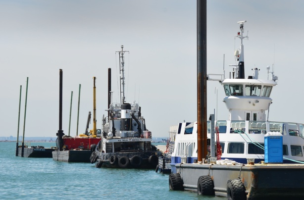 small boats lined up along a dock, tugboat,
