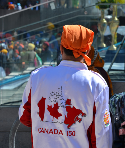 the back of a jacket being worn by a young man, white jacket with red map of canada and the words Canada 150, wearing an orange head scarf tied at the back.