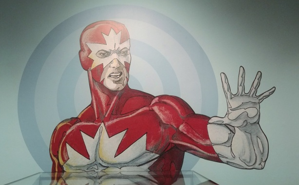 painting of Captain Canuck, from the chest up, one arm raised to shoulder height