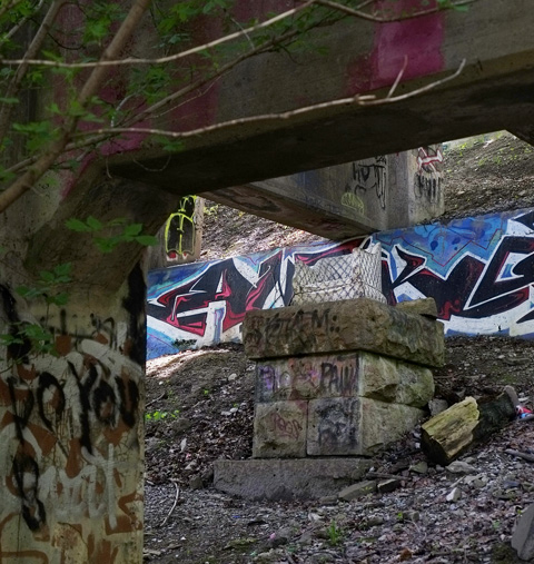 an old stuffed arm chair on a stone pillar under a bridge with graffiti on the bridge supports