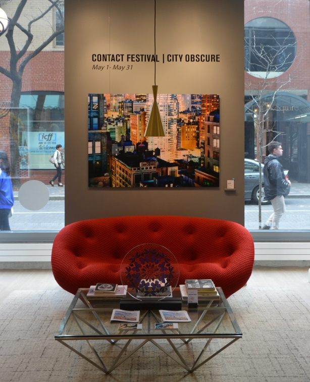 Lomas Gallery in Yorkville, bright red oval shaped couch in front of a wall with a large photo of a city scene, lots of skyscrapers with lots of windows, by Christopher Woodcock, plus words on the wall that say Contact Festival, City Obscure, Windows on either side of the wall with people passing by