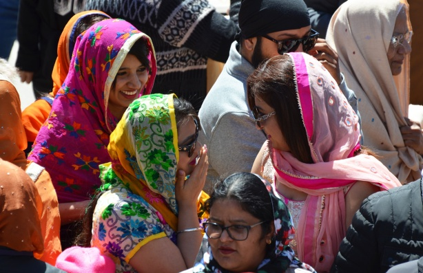 women in a crowd, smiling and talking, wearing sunglasses and colourful saris and head scarves