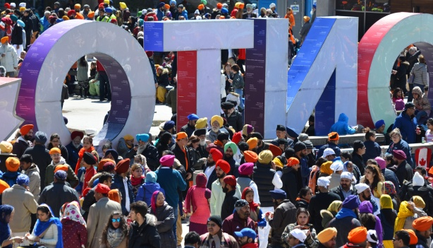 man sikhs in colourful turbans and saris crowd into Nathan Phillips square, and are around the 3D toronto sign, which is backwards in this photo (taken from behind the letters)