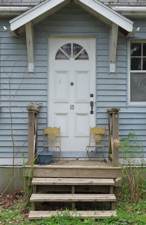 grey wood siding on house with white door and small porch. Two yellow and metal chairs on the porch