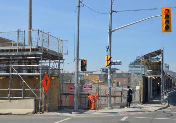 the NW corner of Strachan Ave and East Liberty Street, construction site with fence and hoardings.