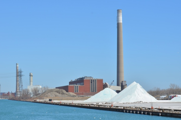 piles of salt on a dock, power generating station in the background.