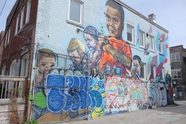 large mural by elicser of kids, bottom part has been covered with three large tags.