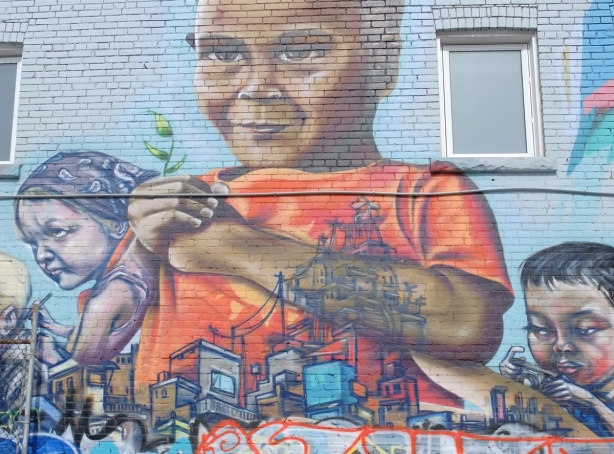 upper part of a mural by elicser showing a boy in an orange t shirt holding a small green sprouting plant in his hands.