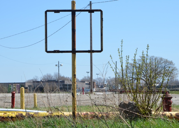 empty rectangular metal frame where a sign once was, on an old yellow rusty pole, vacant land in the background