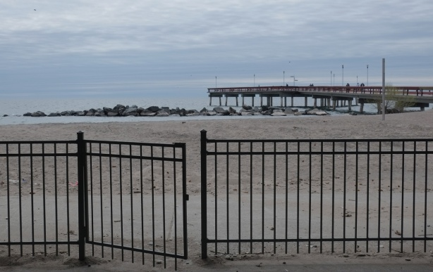 metal fence in the foreground, beach, pier and Lake Ontario in the middle and background