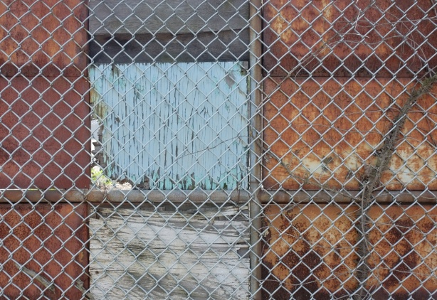 details of a chainlink fence and the old plywood and metal sheeting behind it. peeling paint and rusty metal