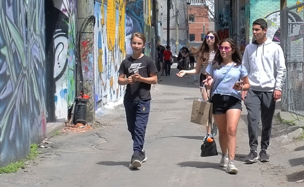 2 young men and 2 young women walking down Graffiti Alley