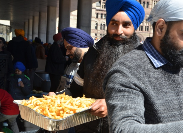 a man in a blue turban and with a long black beard carries a tray of french fries to serve to people