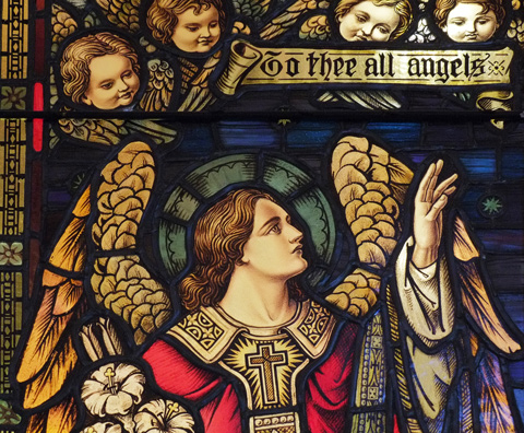 close up of stained glass window, angel, cherub heads, and words that say To thee all angels