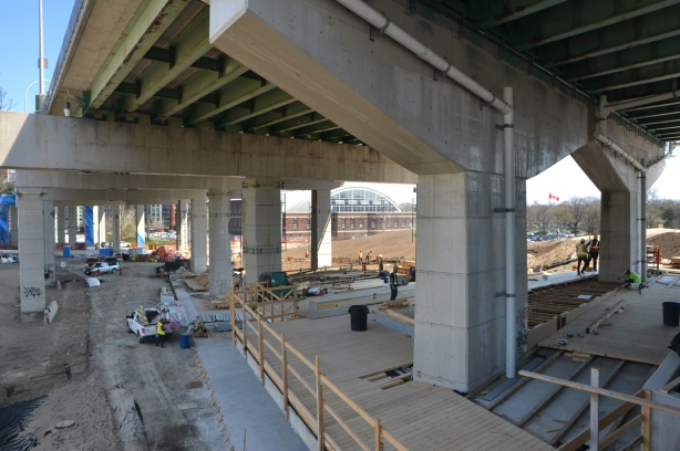 construction under the elevated Gardiner Expressway, making a large set of stairs down from Strachan Ave to Grenadier Common near Fort York