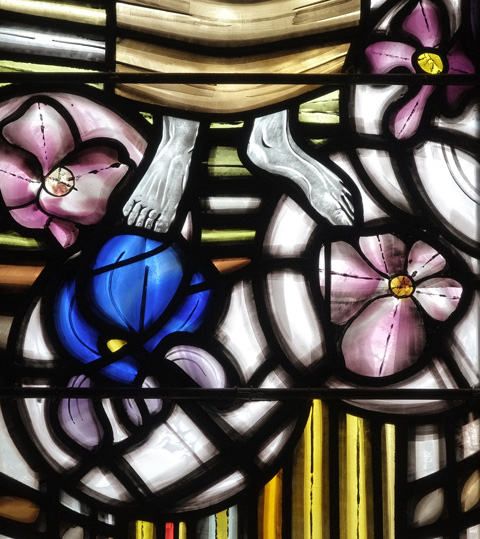 detail of stained glass window, feet and large pink and blue flowers.