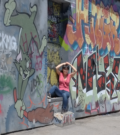 a woman in jeans and pink top poses in the doorway of one of the back doors in Graffiti Alley