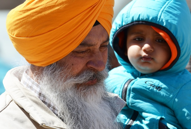 an older sikh man with a long grey beard and an orange turban holds a younger boy in a blue jacket and hood