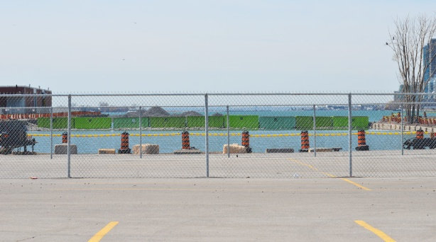 behind a chain link fence, a line of green dumpster bins, laid end to end, stretch across a channel in Lake Ontario,