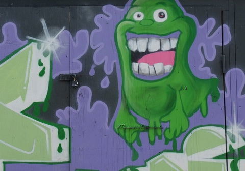 graffiti, purple background, green glob gooey ghost guy with open mouth and big teeth