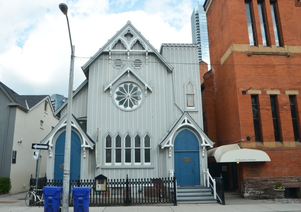 pale blue wood building, originally a church, now the home of the Heliconian Club on Hazelton ave. Bright blue doors, two, rose window,