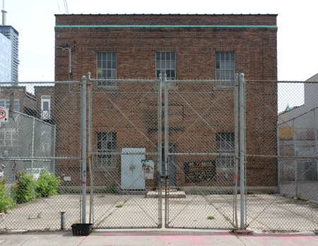 chainlin fence and gate around on old two storey brick building that was part of Toronto Hydro