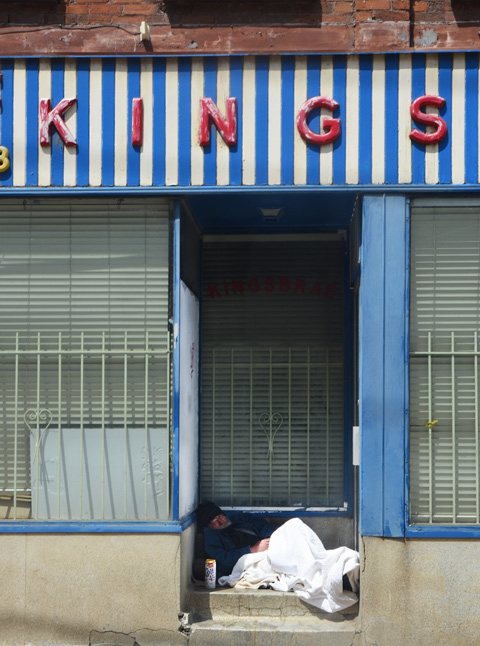 a man under a white blanket is asleep in the doorway of the old Kingsbrae restaurant, with a can of beer beside him