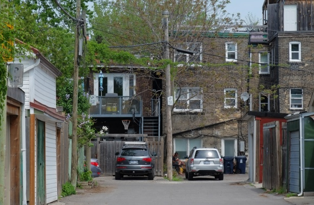 alley view, rear of old three storey brick buildings, apartments on top, stores below, cars parked,