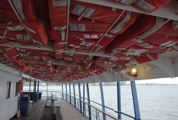 ferry, ceiling is full of orange life jackets, railings along edge, Lake Ontario, benches to sit on but no people