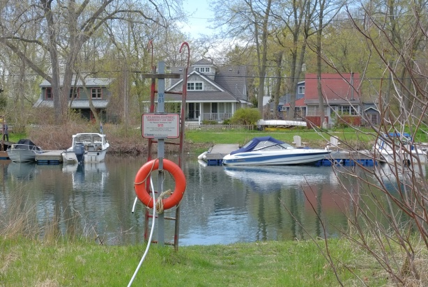 waterway, orange life ring and ladder on one side of the river, houses and docks, and boats on the other. r