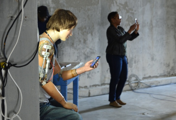 mannequin automatons as part of an art installation in the old Unilever soap factory, concrete floor and walls - sitting on a stool with a phone in one hand, a real woman behind him with a phone in her hand taking a picture