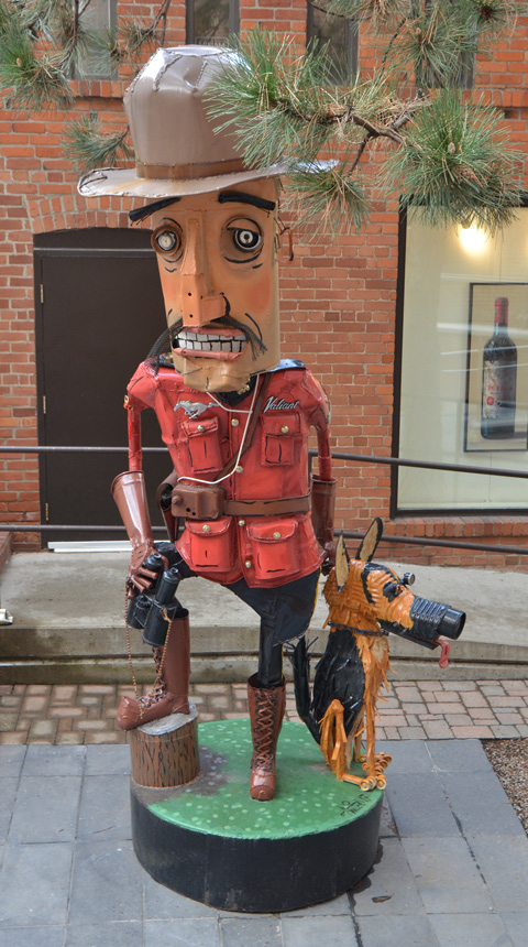metal junk sculpture by Patrick Amiot of a mountie and his dog, outside, behind a gallery in Yorkville