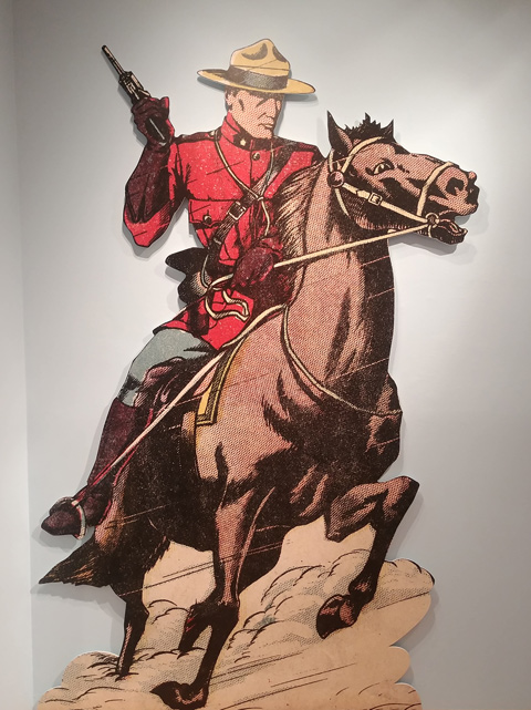 large picture of a mounti on a horse with a gun in his hand, on a wall in a gallery