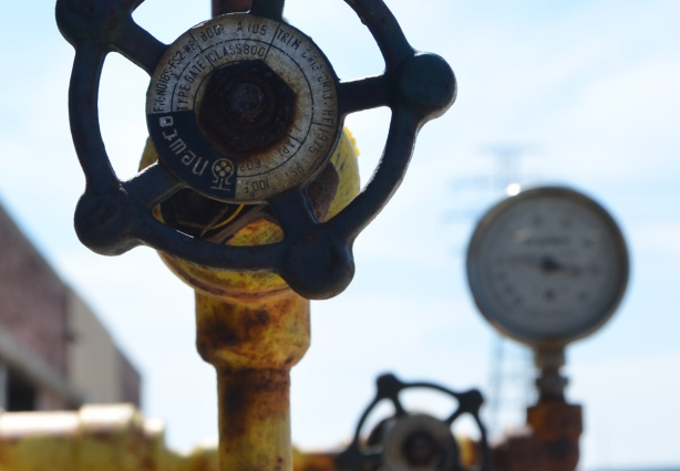 large dial with rust on it, attached to tap on yellow pipe, gauge in the background