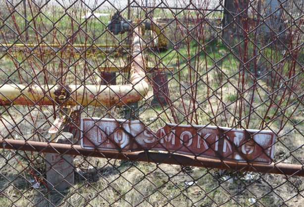 chainlink fence in front of area with yellow pipes, overgrown with weeds and shrubs, sign that says no smoking, white on red, chipped in one corner