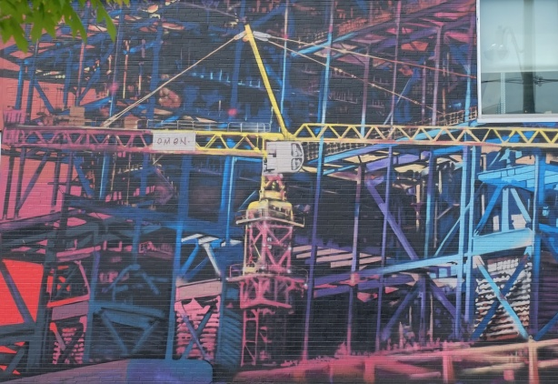 mural of cranes and construction sites on the side of a building, painted by Omen,