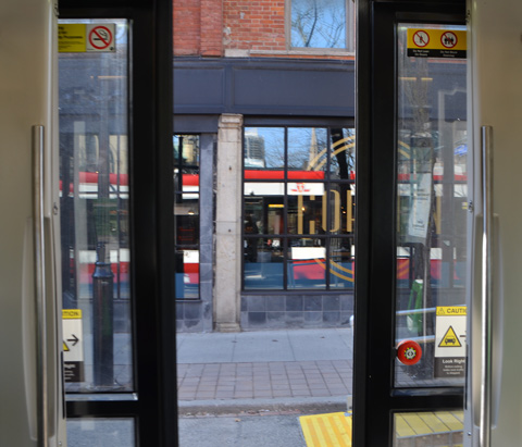 looking out the open doors of a TTC streetcar, as they start to close, see reflection of the streetcar in the window of the store beside the streetcar
