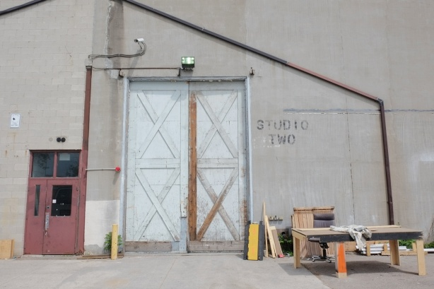 outside a film studio building, large door labelled studio 2, closed doors, some woodworking tools and materials by the door
