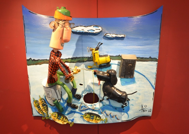 a wall mounted artwork by Patrick Amiot of a man ice fishing with his dog, created from junk