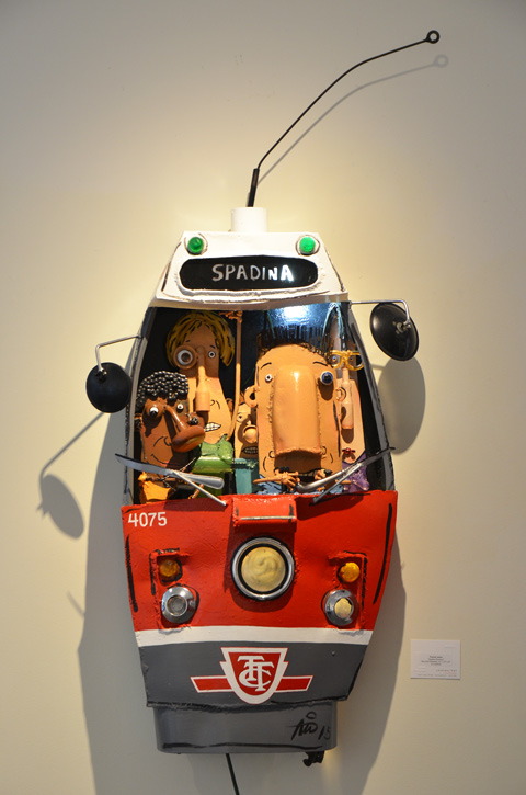 an artwork on a gallery wall, by Patrick Amiot, of the front of a Spadina TTC streetcar, crowded with driver, man, and dog,