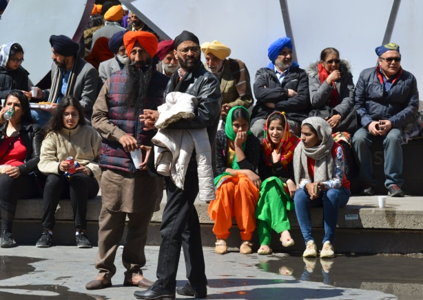 a group of sikhs, men and women, sitting and standing outside