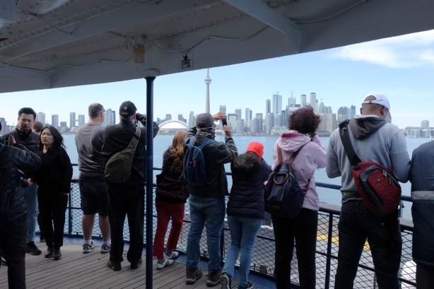 people lined up along the front railing of a ferry from Centre Island to the city of Toronto, looking at skyline and taking picture of it. Toronto is in the background.
