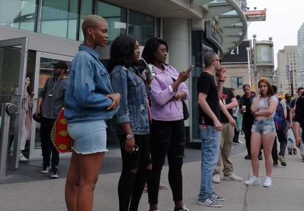 women and men standing outside the Eaton Centre on Yonge street